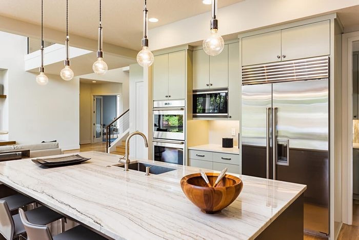 Kitchen in House: Kitchen Interior with Island, Sink, Cabinets, Stainless Steel Refrigerator, Pendant Lights, and Hardwood Floors in New Luxury Home