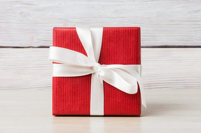Gift box over light wooden background