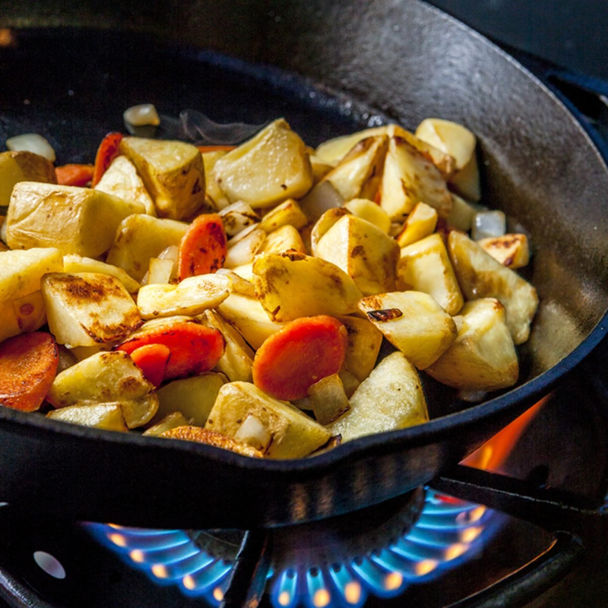 Potatoes in skillet over a fire.