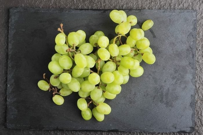 Bunch green grapes on dark background.