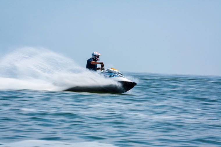Young man professional jet ski rider performs many tricks on the waves.