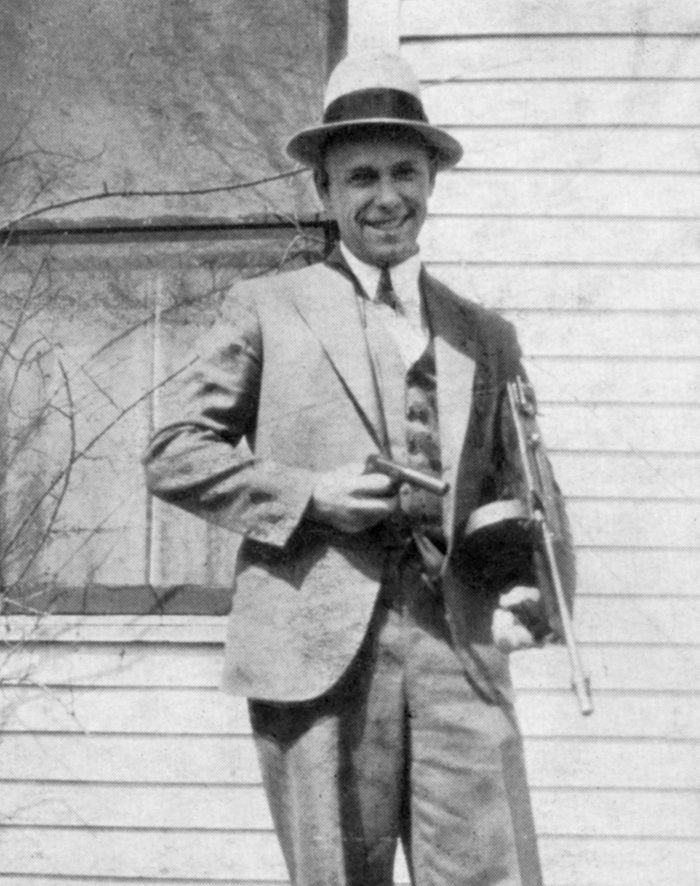VARIOUS John Dillinger (1903-1934), American Gangster, Portrait holding Toy Gun Used to Escape Jail in Crown Point, Indiana, USA, 1934