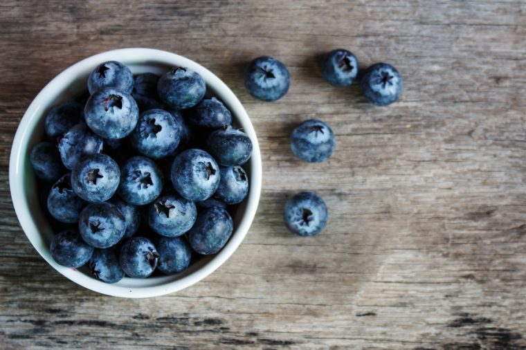 Blueberries in a white bowl on a wooden table