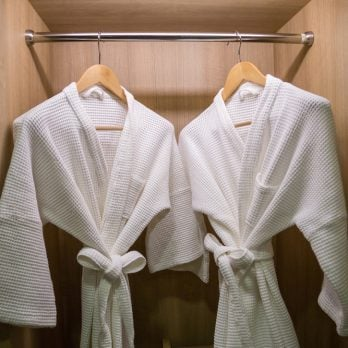two off white color bathrobes hanging in closet, room for copy space