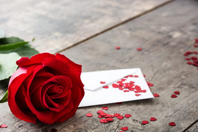 Rose, envelope and hearts on wooden background