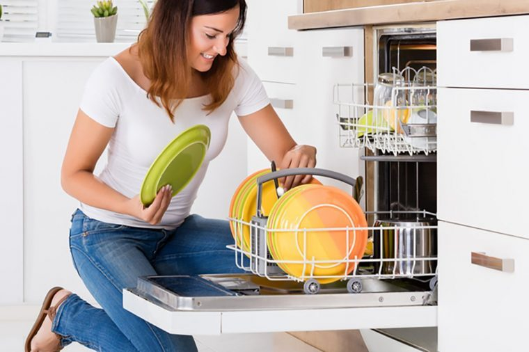 Happy Young Woman Arranging Plates In Dishwasher At Home
