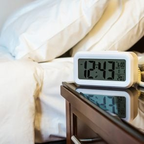 alarm clock on the bedside table in a hotel room