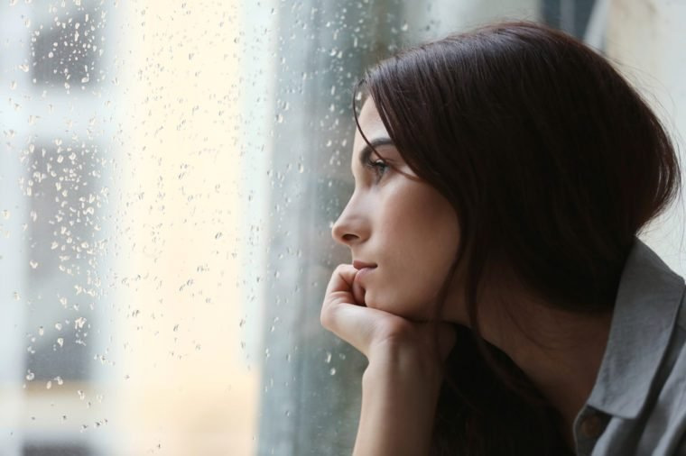 Depressed young woman near window at home, closeup
