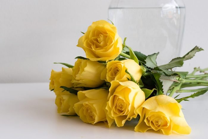 Yellow roses on white table next to glass vase (selective focus)
