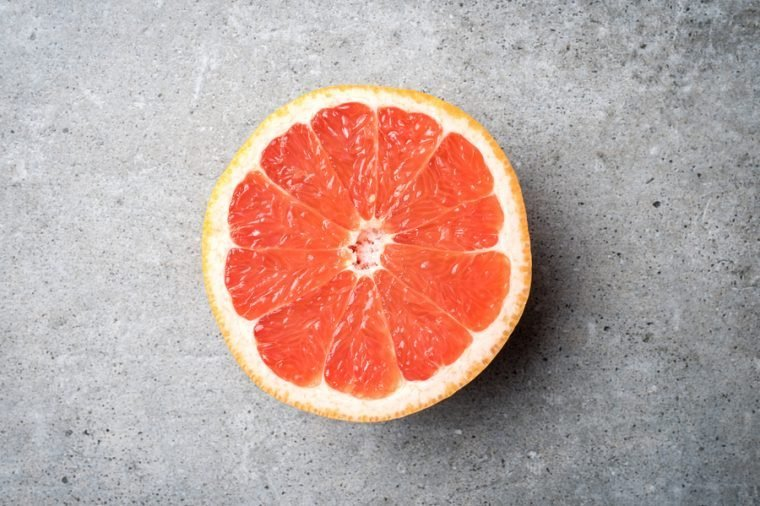 Red grapefruit on stone background