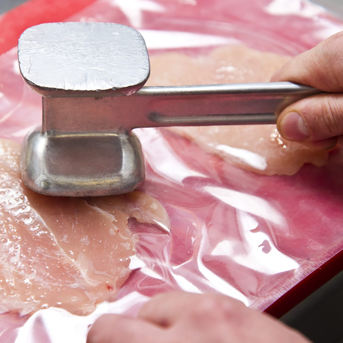 Tenderizing the chicken meat with a mallet - Preparing homemade chicken kiev in a kitchen