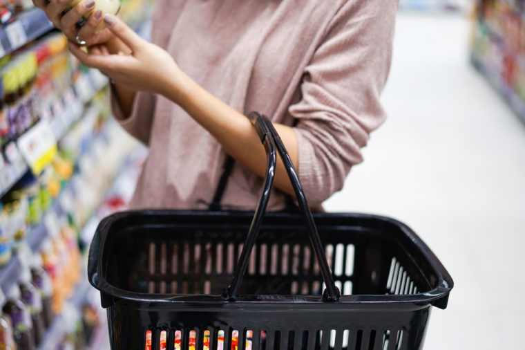 Woman is shopping at the supermarket with the basket to stock item.
