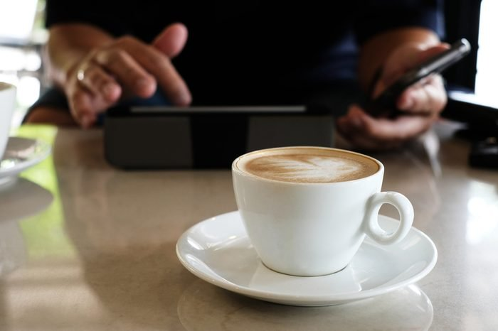 Hot latte coffee in white cup and man use tablet in cafe.