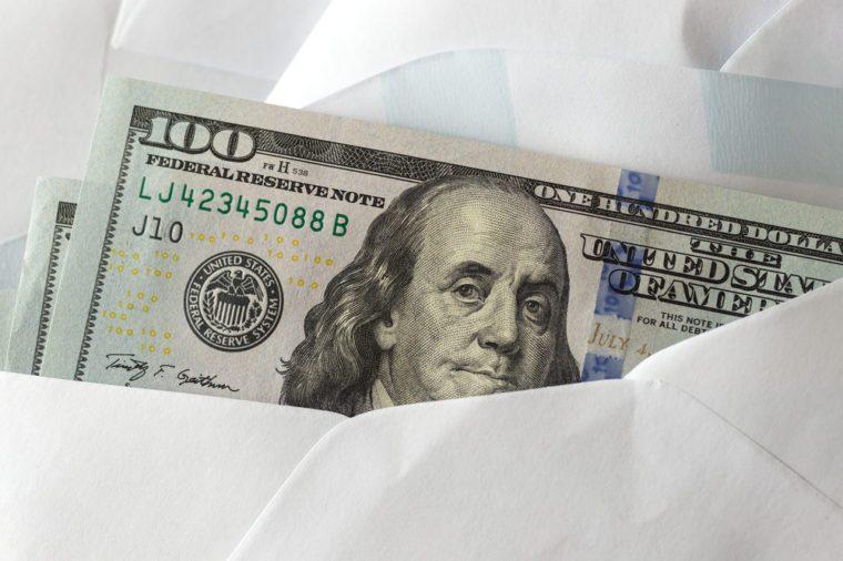 American dollars in envelope at dark background