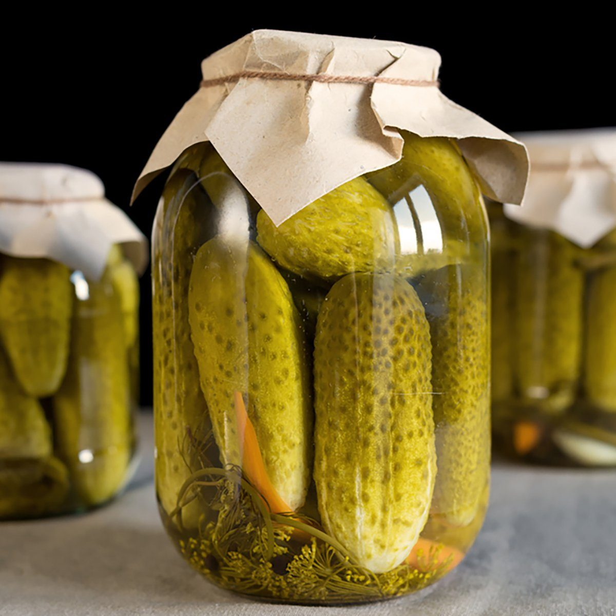 Four glass jars with pickled cucumbers