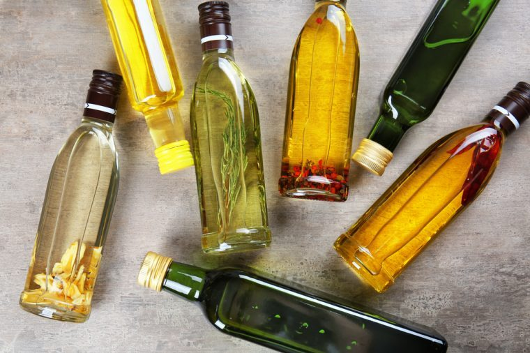 Bottles with different cooking oil on table