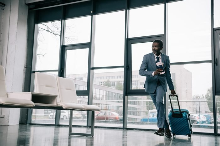 African american businessman hurrying up for flight at airport with wheeled bag