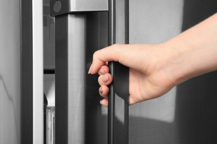 Woman opening refrigerator door, closeup