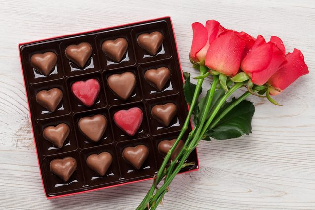 Valentines day greeting card with red roses and heart shaped chocolate on wooden background. Top view