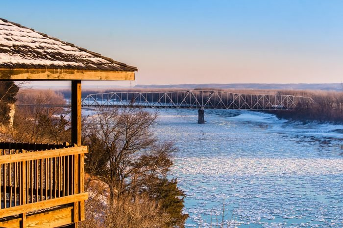 View of the Missouri River on a late winter afternoon; gazebo on the left; highway bridge in the background; floes floating down the river