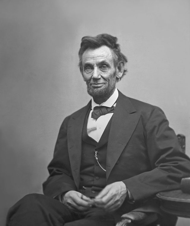 VARIOUS U.S. President Abraham Lincoln, Portrait, Seated next to Table Holding Spectacles and Pencil, Washington DC, USA, by Alexander Gardner, February 1865