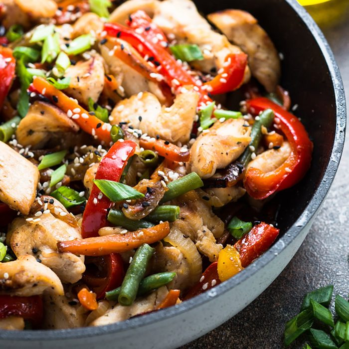 Chicken stir fry with vegetables and sesame in the pan.