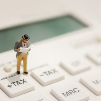 Miniature businessman stand reading on tax button of calculator,  education, financial and business concept.