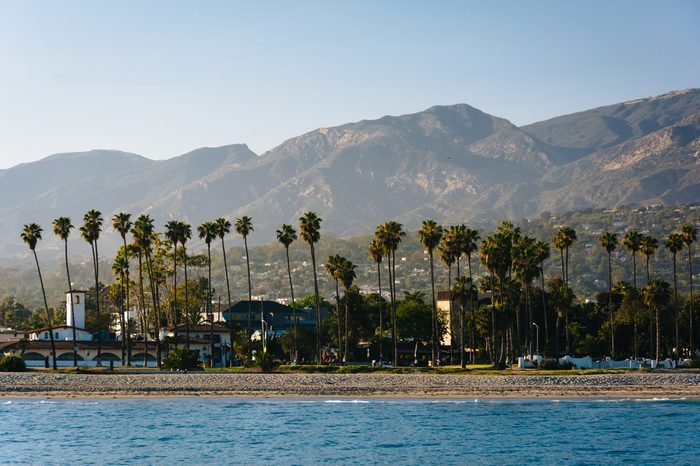 View of palm trees on the shore and mountains from Stearn's Wharf, in Santa Barbara, California.
