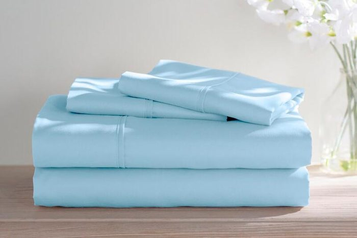 folded sheet set on wooden counter or dresser with a vase of flowers in the background