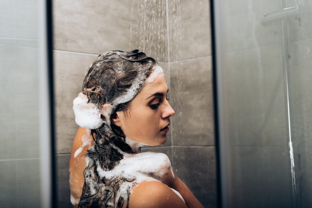 girl washing hair with shampoo in a glass shower cabin