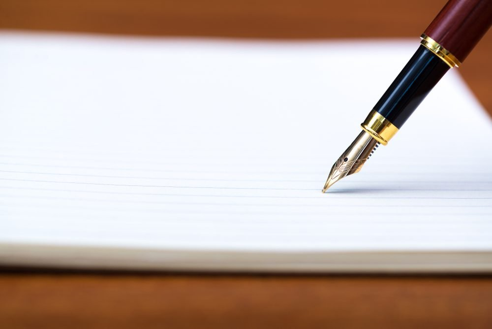 Close up of fountain pen or ink pen with notebook paper on wooden working table with copy space, office desk concept idea. shallow focus.