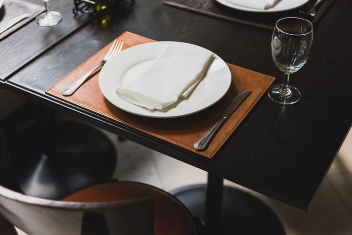 Italian dinner table with cutlery, plate, glass, napkins and naperies with salt and pepper on the table.