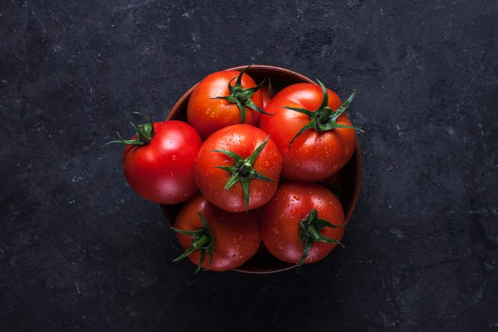 Red, ripe tomatoes on a dark background. Harvesting tomatoes. Top view