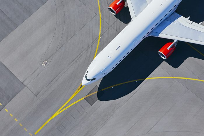 Aerial view of airport. Airplane taxiing to runway before take off.