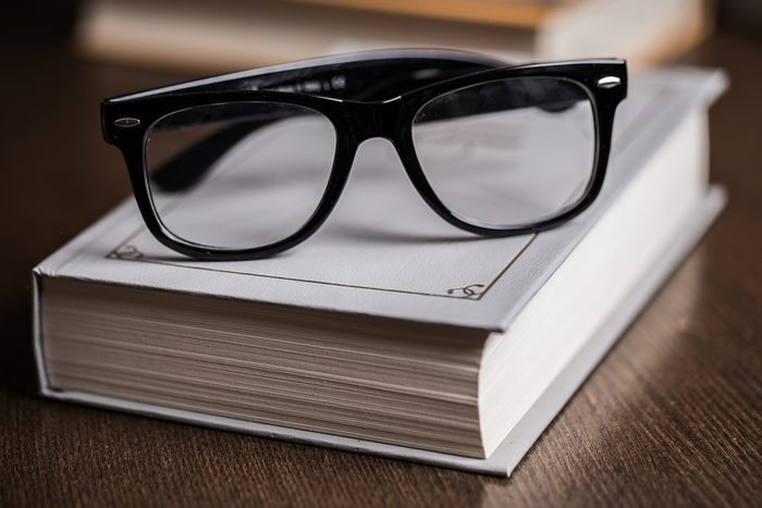 Picture of black glasses on a white book