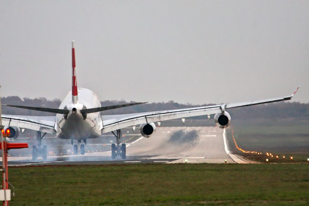 Airplane with four engines landing on runway back view - touchdown with tire smoke
