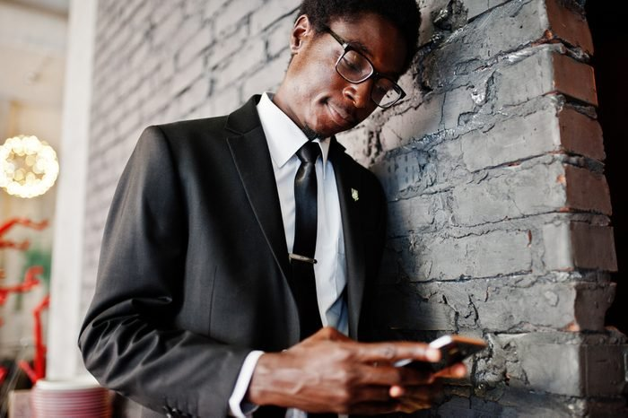 Business african american man wear on black suit and glasses at office looking on mobile phone.