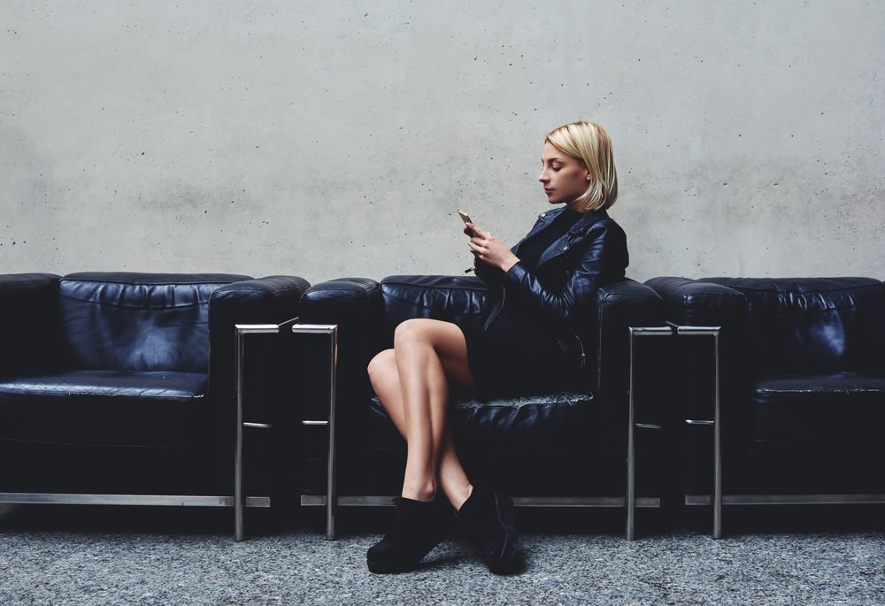 Stylish hipster girl chatting on mobile smart phone with her friend which she awaits before a photo session in the fashion studio, young blonde woman reviewing traffic in Internet via cell telephone