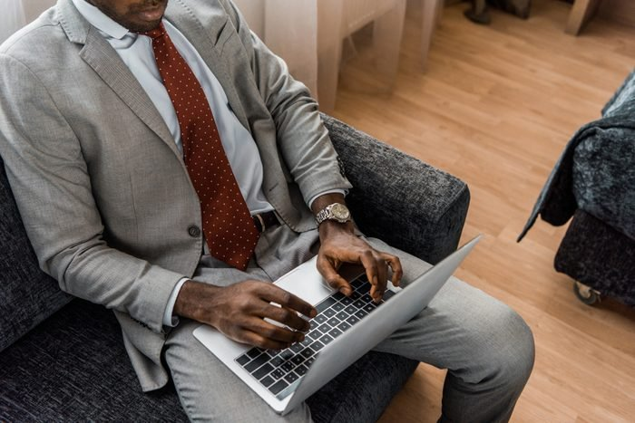 cropped view of african american businessman typing on laptop in hotel room