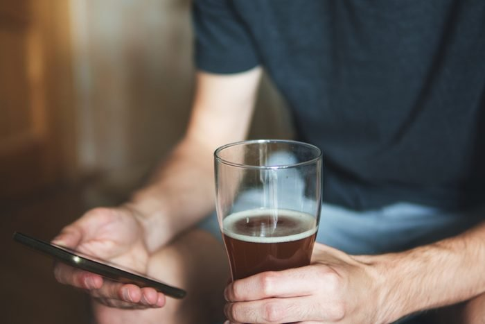 Partial view of a person with alcohol and a phone. Drinks and rests at home
