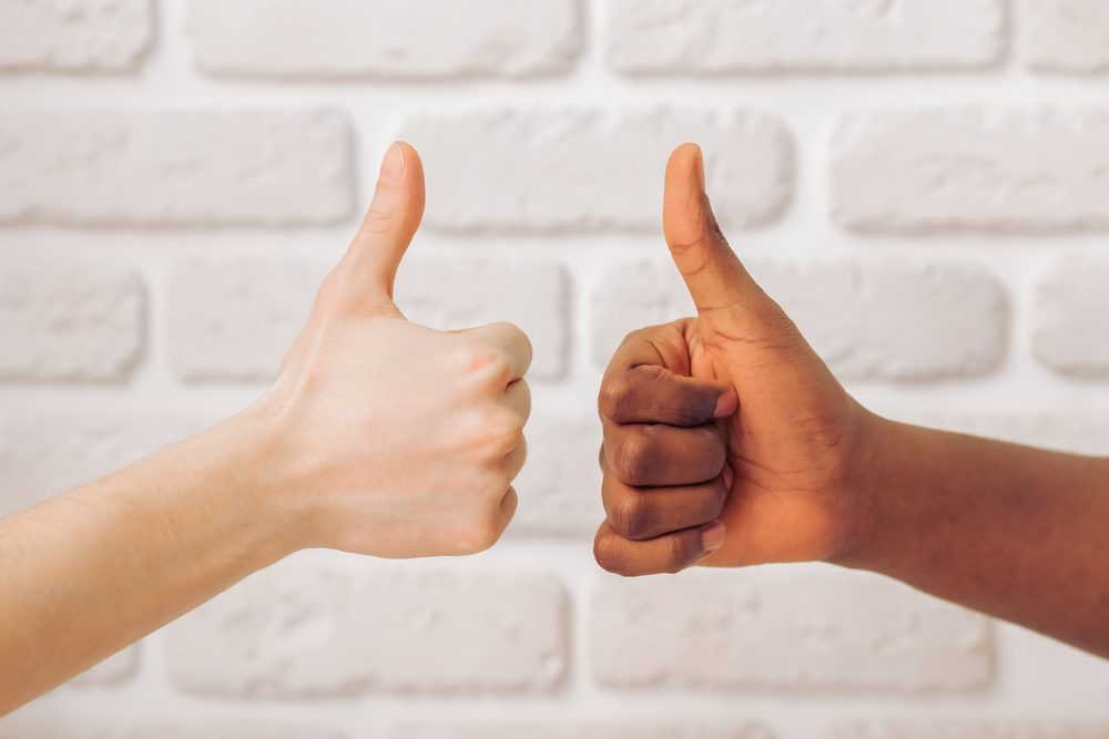 Afro American and caucasian male hands showing Ok sign, against white brick wall, close up