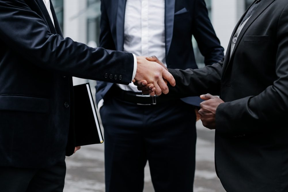 Handshake of business partners. Three businessmen close-up