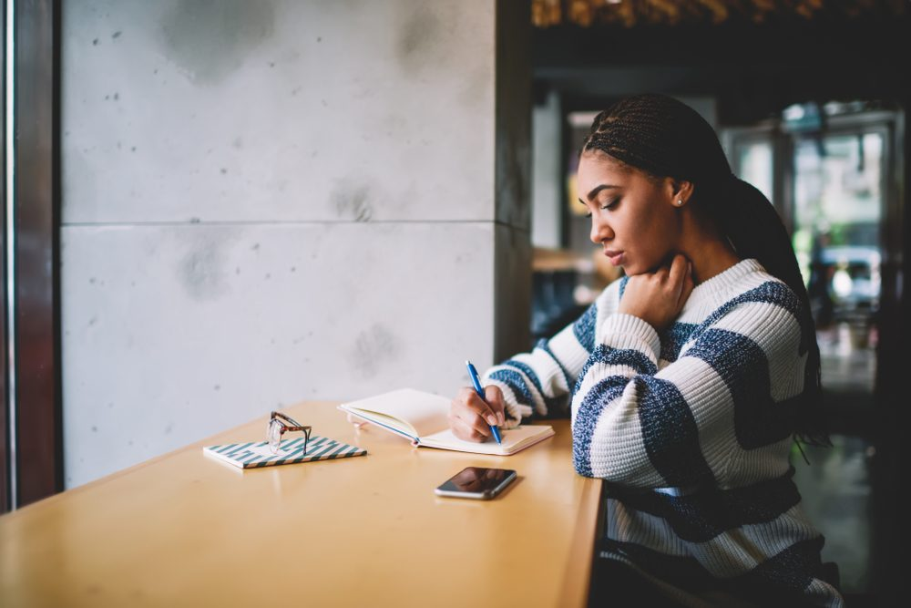 Thoughtful female student writing essay in textbook for education sitting in cafeteria, concentrated african woman studying on autodidact notes information in notepad during free time on leisure