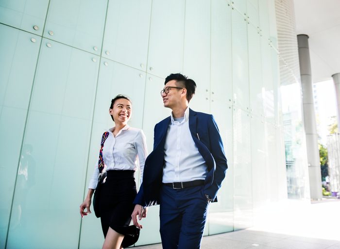 Asian business people discussing while walking