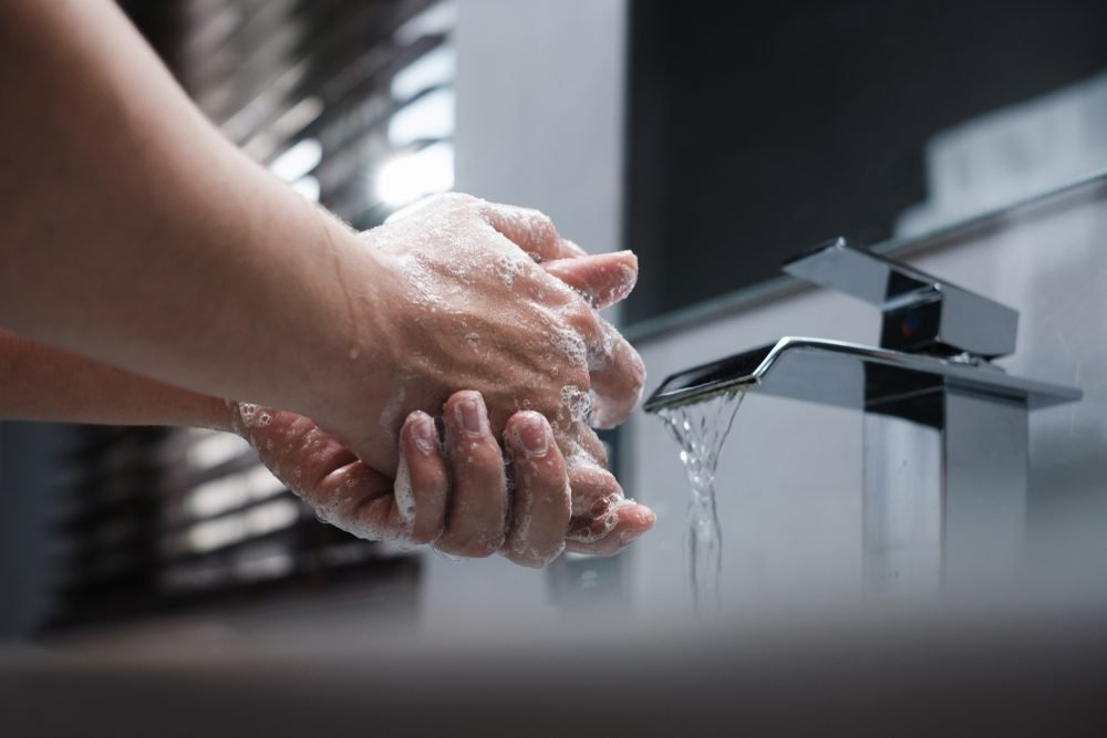 White man lathering and washes his hands with soap in the restroom while keeping the faucet water running. Concept for body hygiene, disease prevention, personal hygiene, and bathroom activity