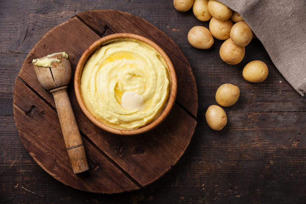 Wooden bowl with mashed potatoes and raw potatoes on dark background