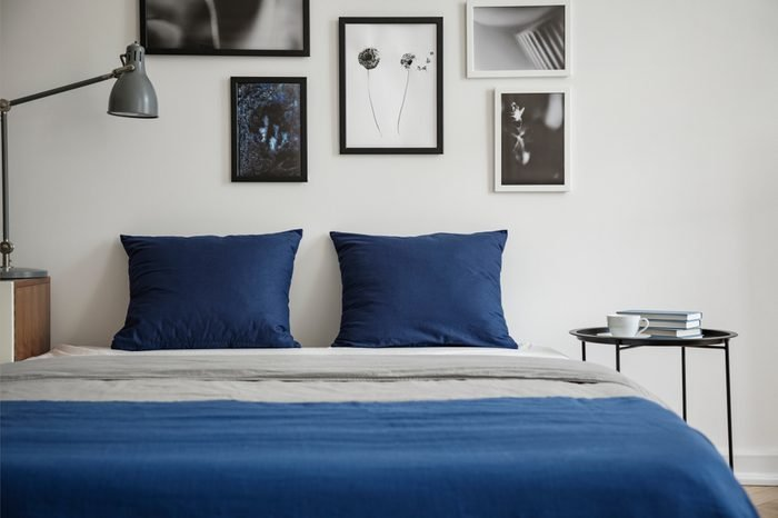 Navy blue pillows on bed between table and lamp in white bedroom interior with posters. Real photo