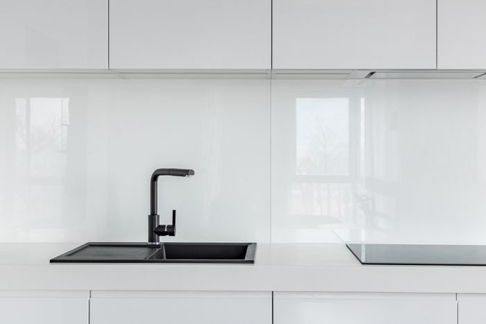 High gloss cabinets, countertop and black composite kitchen sink