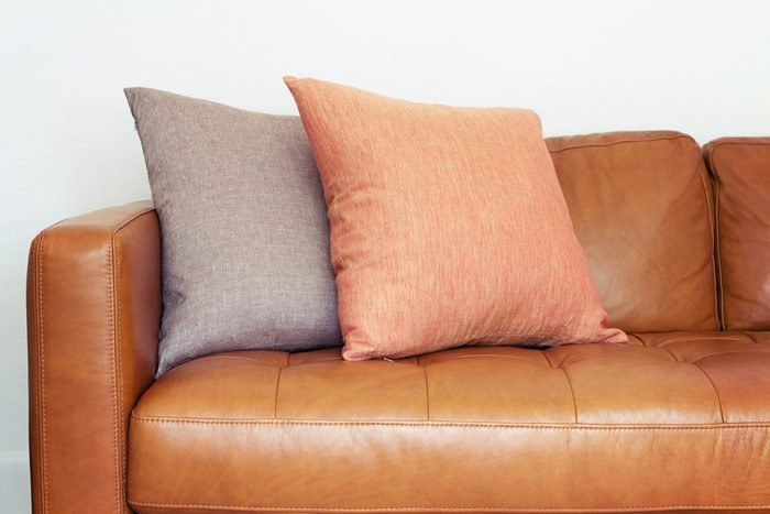 Close up of tan leather sofa with two linen cushions