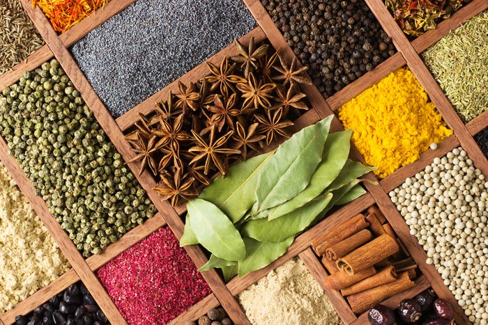 Spices and herbs for decorating food labels . Seasoning in wooden box as background, top view.